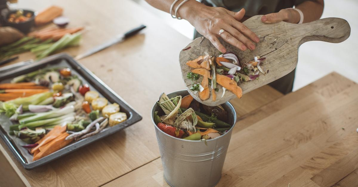 Home composting: a person's hands are shown brushing food scraps into a compost bucket